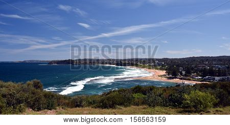Mona Vale rock pool in a distant panoramic view from elevated lookout during high tide surfing waves and sandy beach australia sydney northern beaches
