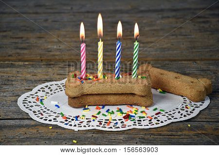 birthday candles in dog bone with candy sprinkles on lace paper doily