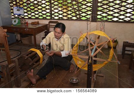 SIEM REAP CAMBODIA - OCT 21 2016: A weaver adjusts the silk cloth on his loom near Siem Reap Cambodia