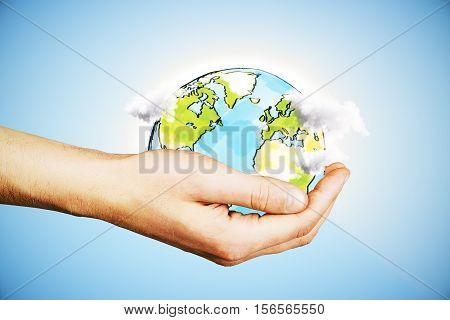 Hand holding creative drawn terrestrial globe with clouds on blue background. Eco concept