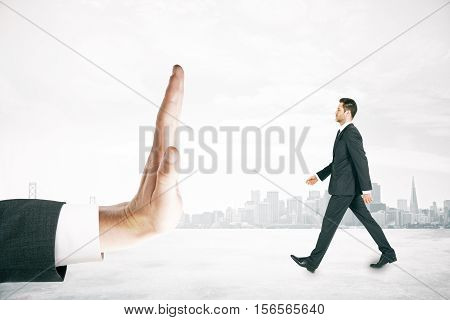 Hand stopping walking businessman miniature on city background