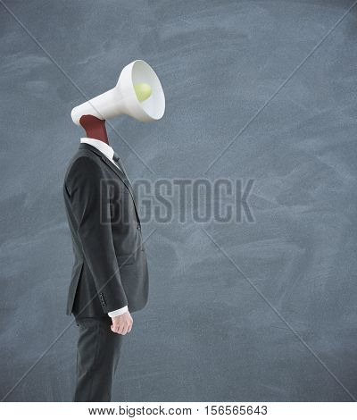 Loud speaker headed businessman on chalkboard background. Communication voice and power concept