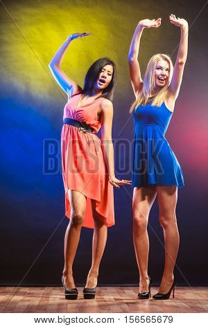 Party celabration carnival. Two attractive funny dancing women in dresses on colorful background in studio.