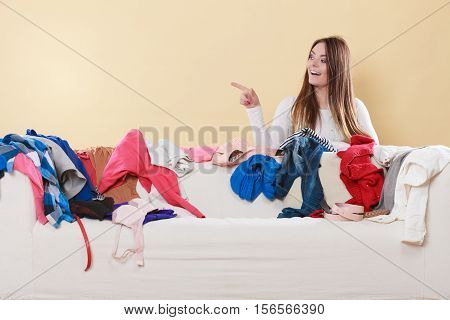 Happy woman behind sofa couch in messy living room pointing at empty blank copy space. Young girl surrounded by many stack of clothes. Disorder and mess at home.