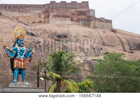 Dindigul India - October 23 2013: Large mainly blue colorful bloody cruel goddess Kali statue at the foot of the Rock Fort. Ramparts are backdrop. Green foliage. Beige and browns background.