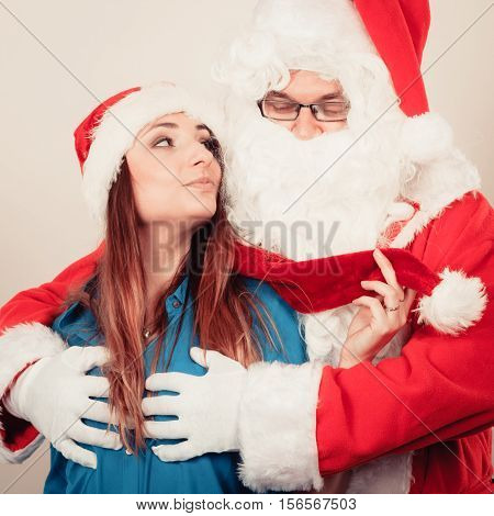 Christmas holiday concept. Man wearing Santa Claus costume touching woman in christmassy hat.