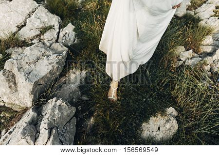 a girl in white dress stepping on the grass