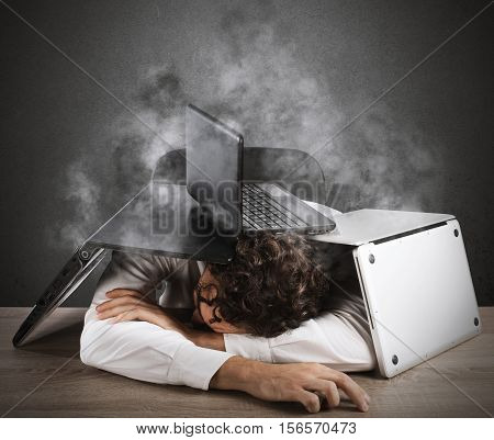 Tired businessman sleeping under a pile of computers