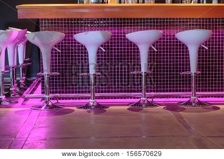 amazing fragment of view of cozy illuminated comfortable stylish bar seats in the basement
