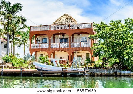 Placencia, Belize - August 28 2016: Tropical waterside house with moored boat on lagoon side of Placencia in Belize, Central America