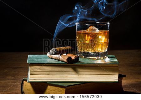 Cigar With Blue Smoke And Whisky On Ice And Two Books Volume