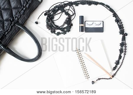 Flat lay of empty notebook pencil and woman's accessories in black concept top view isolated on white background