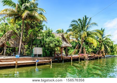 Placencia, Belize - August 28 2016: Tropical waterside palapas on lagoon side of Placencia in Belize, Central America