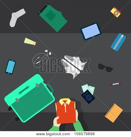 Someone packing his stuff for travel in an opened suitcase. He puts in suitcase clothes shoes glasses cosmetics camera and passport. Camera top view.