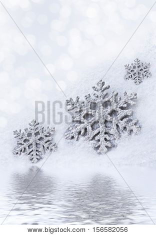 Glass toy snowflake on snow background. New Year card.