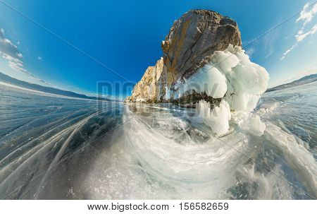 Rock on Olkhon Island on Lake Baikal ice covered on aerial fisheye.