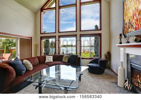 American Living Room With High Vaulted Ceiling And Water View