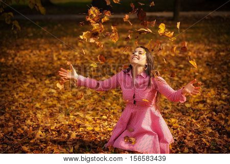 season and people concept - beautiful happy young woman having fun with leaves in autumn park