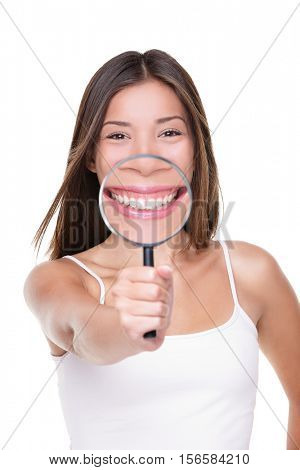 Funny woman showing perfect smile and white teeth with magnifying glass for closeup dental concept. Asian girl inspecting details of mouth showing healthy tooth care for dentist.