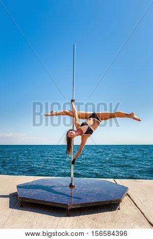 Female pole dancer against the sea and sky