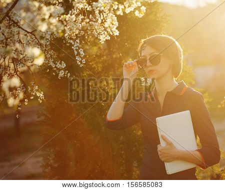 Cute girl holding a laptop in hand. Portrait against the setting sun and cherry blossoms. She straightens sunglasses