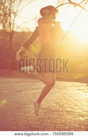 Cute girl jumping on a sunset background. Warm toning. Walk alone.