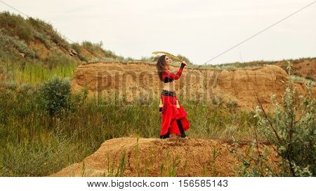 Oriental Beauty dance with a sword. Tribal style. Attractive girl in costume dancing outdoors. Sand dunes. Nomads.