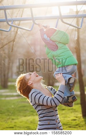 Mom help son to the horizontal bars in the autumn park. Family time. Happiness of childhood and parenthood. Outdoor Activities.