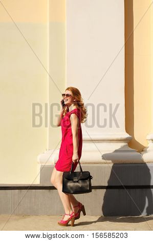 Girl in red dress sunglasses with curly hair and trendy bag. Girl talking on the phone. Urban fashion.