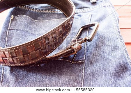 Leather belt on the jeans background. Braided belt with metal buckle.