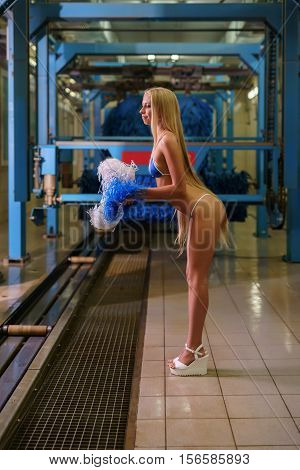 At car wash. Image of long-haired blonde posing with pom-poms