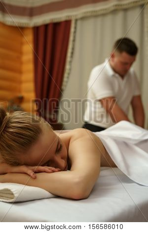 In wellness center. Portrait of young woman getting massage