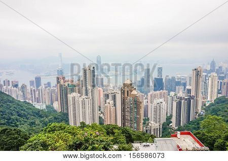 High view of cityscape of modern city with green trees and mist in hong kong