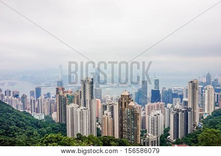 High view of cityscape of modern city with green trees and mist in hong kong. Business concept for real estate and corporate construction