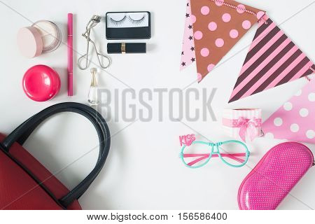 Overhead view of essential beauty items Top view of party accessories red hand bag fashion eyeglasses and cosmetics top view isolated on white background