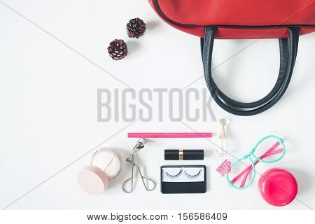 Overhead view of essential beauty items Top view of red hand bag fashion eyeglasses and cosmetics top view isolated on white background