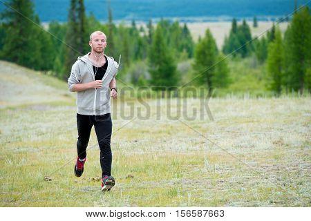 Man running on grass field at mountain background.
