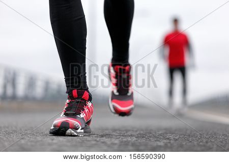 Running shoes - closeup of male runners running on winter street. Sport fitness athlete man jogging outdoors on city road in cold weather.