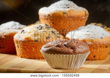 Some muffins with caster sugar on black background