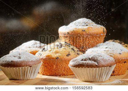 Sprinkling caster sugar on some muffins on black background