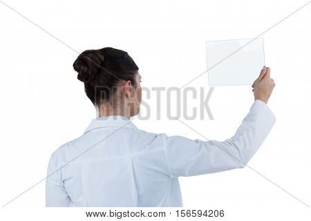 Rear view of female doctor holding digital tablet against white background