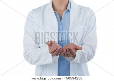 Mid-section of female doctor standing with hands cupped against white background