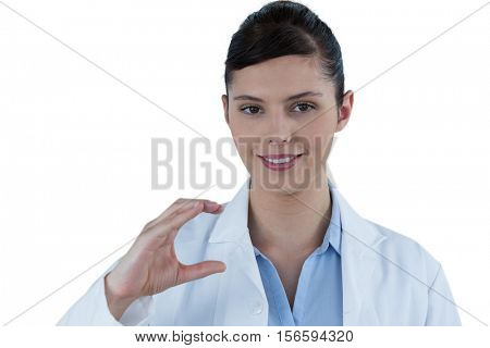 Beautiful female doctor gesturing against white background