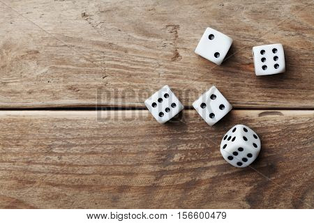 White dice on wooden table top view. Gambling devices. Game of chance concept.