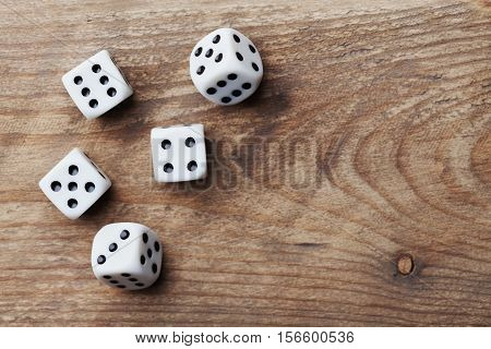 White dice on wooden table from above. Gambling devices. Game of chance concept.