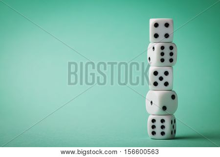 White dice on green background. Gambling devices. Copy space for text. Game of chance concept.