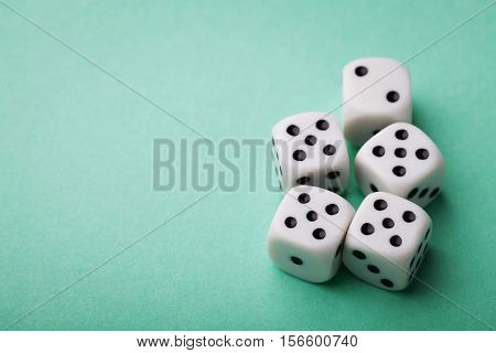 White dice on green table. Gambling devices. Copy space for text. Game of chance concept.