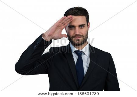 Portrait of businessman saluting against white background