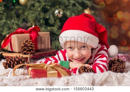 smiling happy boy in elf hat with christmas presents by the tree waiting for a miracle at holiday time