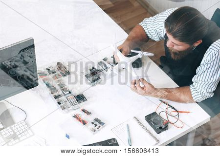 Top view on repairman with drone, double exposure. Engineer construct propellers on quadrocopter, free space on white table. Electronic toy repair shop